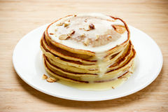 Bunten av pannkakor med förtätat mjölkar och muttrar på en vit platta Royaltyfria Foton