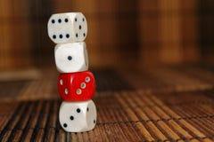 Bunten av plast- för tre vit tärnar och röd tärning en på brun träbrädebakgrund Sex sidokub med svarta prickar Nummer 1, 3, royaltyfria foton