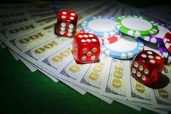 Bunten av pokerchiper med tärning rullar på räkningar för en dollar, pengar Pokertabell på kasinot Begrepp för pokerlek Spela en  Fotografering för Bildbyråer