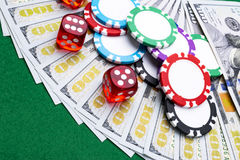 Bunten av pokerchiper med tärning rullar på räkningar för en dollar, pengar Pokertabell på kasinot Begrepp för pokerlek modigt le Royaltyfri Fotografi