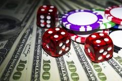 Bunten av pokerchiper med tärning rullar på räkningar för en dollar, pengar Pokertabell på kasinot Begrepp för pokerlek modigt le Royaltyfri Bild