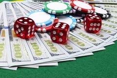 Bunten av pokerchiper med tärning rullar på räkningar för en dollar, pengar Pokertabell på kasinot Begrepp för pokerlek modigt le Royaltyfri Foto
