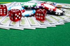 Bunten av pokerchiper med tärning rullar på räkningar för en dollar, pengar Pokertabell på kasinot Begrepp för pokerlek modigt le Royaltyfria Foton