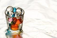 Bunten för vodka fylls med hydrogelbollar av olika färger Royaltyfri Foto