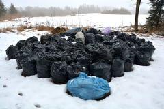Bunten rackar ner på avfall som fulla plast- säckar på insnöat parkerar Arkivfoto