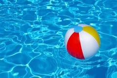 Bunter aufblasbarer Ball, der in Swimmingpool schwimmt Lizenzfreie Stockfotografie