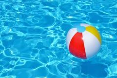 Bunter aufblasbarer Ball, der in Swimmingpool schwimmt Stockfotografie