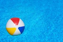 Bunter aufblasbarer Ball, der in Swimmingpool schwimmt Lizenzfreie Stockbilder