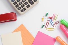 Bunter Büroartikel mit Taschenrechner und rotem Hefter lizenzfreie stockfotografie
