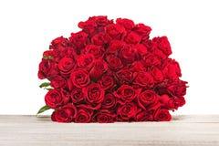 Bunter Blumenblumenstrauß von den roten Rosen lokalisiert auf hölzernem backgr Lizenzfreies Stockbild