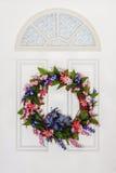 Bunter Blumensommer-Kranz, der an der weißen Tür hängt Lizenzfreies Stockfoto