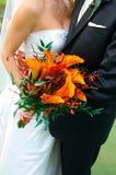 Bunter Blumenstrauß angehalten von einer Braut und von einem Bräutigam Stockbilder