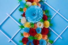 Bunter Blumenstrauß gemacht mit Papier auf einer blauen Oberfläche stockbild