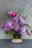 Bunter Blumenstrauß im Glasvase mit purpurroter Flieder, rosa Tulpe und stockfoto