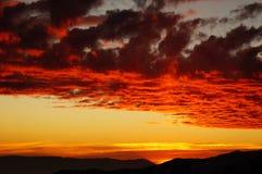 Bunter brennender Sonnenuntergang über den Bergen Stockfotos