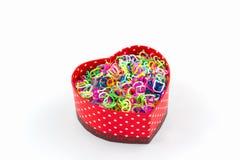 Bunter elastischer Regenbogenwebstuhl versieht in kastenförmigem Herzen des Geschenks mit einem Band Lizenzfreies Stockbild