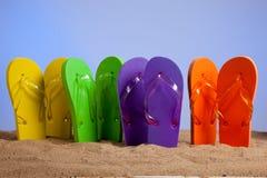Bunter Flipflop Sandles auf einem Sandy-Strand lizenzfreies stockbild