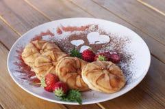 Bunter Frühstücksteller mit Pfannkuchen, Beeren und Kakaopulver mit Herzen auf Holztisch stockfotografie
