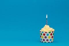 Bunter Geburtstagskleiner kuchen mit blauer Kerze Stockfotografie