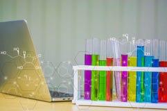 Bunter Glasbehälter gelegt nahe einem Laptop in Labor und in eine chemische Ikone Mit dem Konzept der Forschung und der Erfindung Lizenzfreies Stockfoto