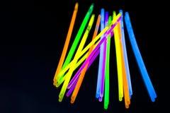 Bunter großer Glühenneonstock des Leuchtstofflichtes auf Spiegelreflexionsschwarzhintergrund stockfoto