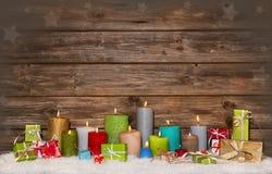 Bunter hölzerner Weihnachtshintergrund mit Kerzen und Geschenken Stockfotografie