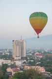 Bunter Heißluft-Ballon im Flug über der Stadt Lizenzfreies Stockbild