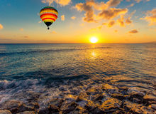 Bunter Heißluftballon über dem Meer bei Sonnenuntergang Lizenzfreie Stockfotografie