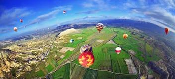 Bunter Heißluftballon, der über Felsenlandschaft im blauen Himmel fliegt Stockbild