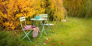 Bunter Herbstgartenwinkel mit heißem Tee und Decke Stockfotos