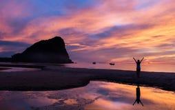 Bunter Himmel auf Sonnenaufgang und Leute am Strand Stockbilder