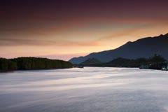 Bunter Himmel des Sonnenuntergangs, der über Oberfläche von Ozean nachdenkt lizenzfreie stockbilder