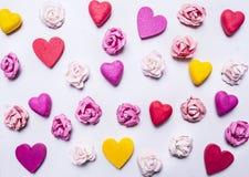Bunter Hintergrund von Herzen und von Papierrosen an einem weißen hölzernen Hintergrund Valentinstag Stockbild