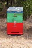 Bunter Honey Beehive im Wiesen-Abschluss oben Rot-, Grüner und Blau gemalterbienen-Bienenstock nahe bei einem Kiefern-Wald im Som Lizenzfreie Stockfotografie