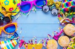 Bunter Karnevalsrahmen des Zubehörs, der Ausläufer, des Parteihutes und der Konfettis auf blauen hölzernen Planken mit Kopienraum Stockfoto