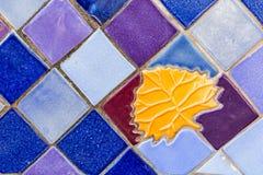 Bunter Keramikziegel-Hintergrund mit goldener Blatt-Einfügung Stockfotos