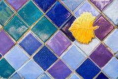 Bunter Keramikziegel-Hintergrund mit goldener Blatt-Einfügung Stockfoto