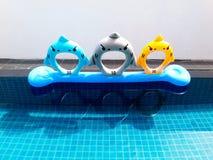 Bunter oder netter Rettungsring, der mit Reflexion auf dem blauen Swimmingpool mit weißem Wandhintergrund schwimmt Stockbild