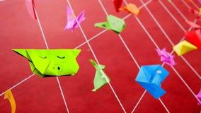 Bunter Origami durch Kinder auf dem roten Gebiet stockfoto