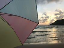 Bunter Pastellregenschirm mit Sonnenuntergangszene am Strand mit ruhiger Welle stockbild
