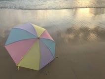 Bunter Pastellregenschirm und das Meer stockfotografie