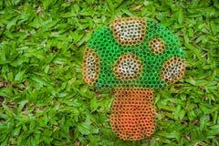 Bunter Pilz auf dem grünen Gras handgemacht mit Plastikstroh Stockbild