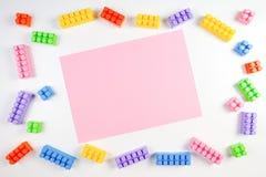 Bunter Plastikbau blockiert Rahmen mit rosa leerer Karte auf weißem Hintergrund Stockfotografie