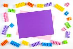 Bunter Plastikbau blockiert Rahmen mit violetter leerer Karte auf weißem Hintergrund Stockbilder