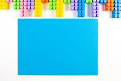 Bunter Plastikbau blockiert Rahmen und blaue leere Karte auf weißem Hintergrund Stockfoto