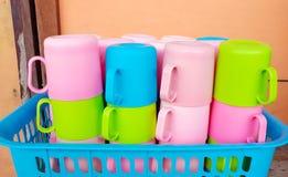 Bunter Plastikbecher vereinbaren im Plastikkorb Stockbilder