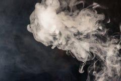 Bunter Rauch auf einem schwarzen Hintergrund von roten und weißen Farben Th stockfotos