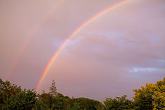 Bunter Regenbogen im bewölkten Himmel Lizenzfreies Stockfoto