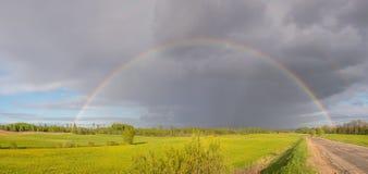 Bunter Regenbogen nach dem Sturm, der über ein Feld nahe der Straße überschreitet Stockbild