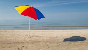 Bunter Regenschirm auf Strand stockfoto